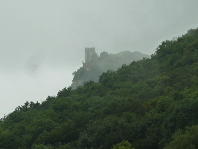 Castle ruin on the hill in the misty rain.