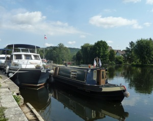 A English narrow boat rafted up to us so that the captain could visit the boulangerie. John stopped for a cup of coffee before heading away.